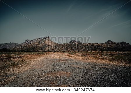 Country Road In The Mountains . A Wide Empty Road In The Desert Toward Distant Mountains . Gravel An