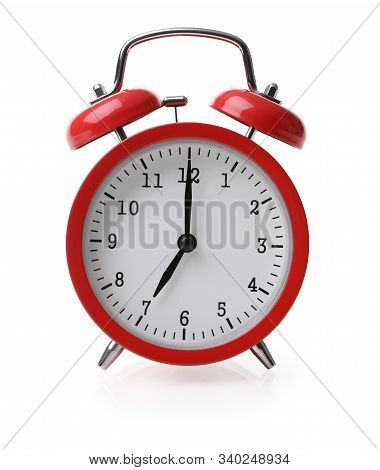 Red Alarm Clock Set At Seven Isolaten Over White Background Close-up