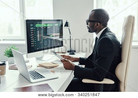 Concentrated Young African Man In Formalwear Using Modern Technologies While Working In The Office