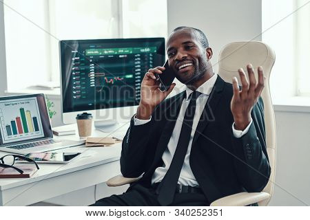 Happy Young African Man In Formalwear Talking On The Phone And Smiling While Working In The Office