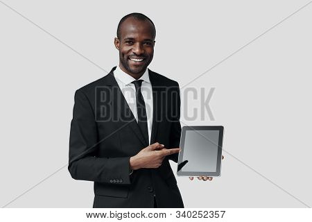 Confident Young African Man In Formalwear Pointing Copy Space On Digital Tablet While Standing Again