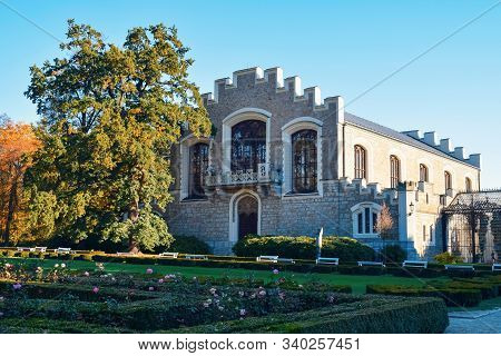 Ancient Stone Building With Battlements On Roof In A Park In Europe In Autumn