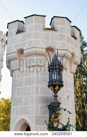 Antique Lantern On The Wall Of An Ancient Castle With Battlements On The Roof For Defense In Europe