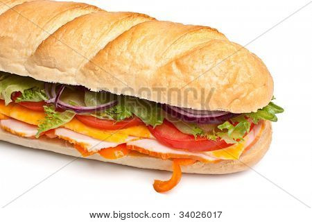 long baguette sandwich with lettuce, slices of fresh vegetables, ham, turkey breast and cheese