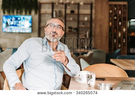 Middle Aged Bearded Man Drinking First Morning Coffee And Smoking On His Job Break In A Cafe. Busine