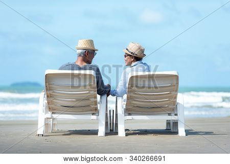 Asian Lifestyle Senior Couple Sitting On The Chair Beach.  People Old Happy In Love Romantic And Rel