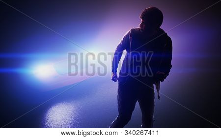 Silhouette Of Man Running Away From Car On Road At Night.