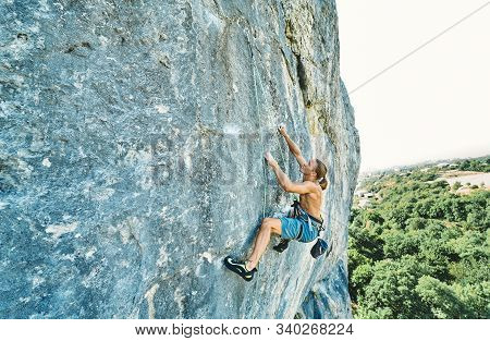 Muscular Man Rockclimber With Naked Torso Climbing On Tough Sport Route.