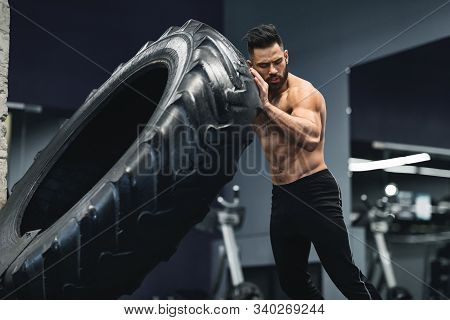 Functional Training. Shirtless Muscular Guy Flipping Huge Tire At Gym, Free Space