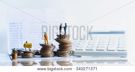 Miniature People Standing On A Pile Of Coins. Inequality And Social Class. Income And Economic Inequ