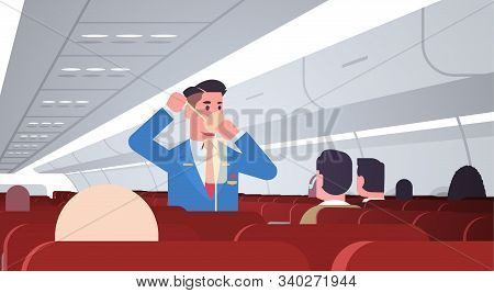 Steward Explaining For Passengers How To Use Oxygen Mask In Emergency Situation Male Flight Attendan