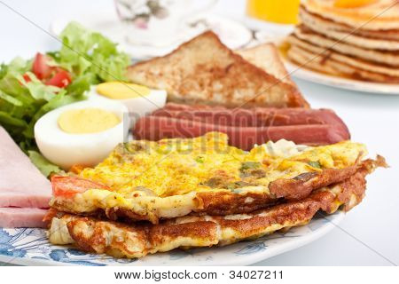 omelette with ham, bacon and vegetables close up
