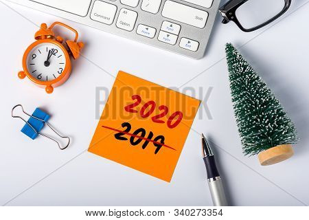 Business New Year Concept - Little Christmas Tree With Message 2020 Is Replacing 2019 On Office Desk