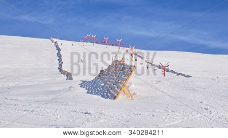 Sinaia ski domain. View of a medium difficulty slope in Valea Dorului, a wooden protection fence, and an old, red, chairlift. Popular Winter resort in Bucegi mountains, Romania. poster