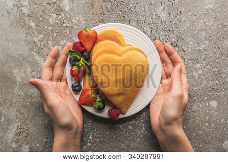 Partial View Of Woman Holding Plate With Heart Shaped Pancakes And Tasty Berries On Grey Concrete Su