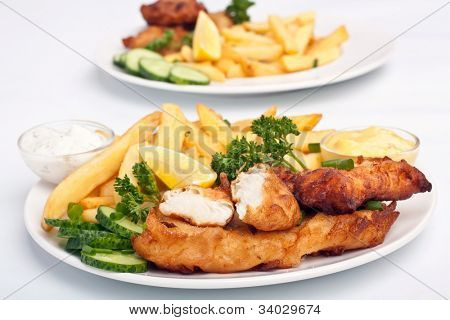 two servings of fish and chips on white background