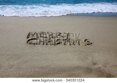 Christmas Words in beach sand. The words Merry Christmas written in the beach sand. Pacific ocean waves and blue ocean water and sky in the background. Christmas at the beach. Laguna Beach CA.