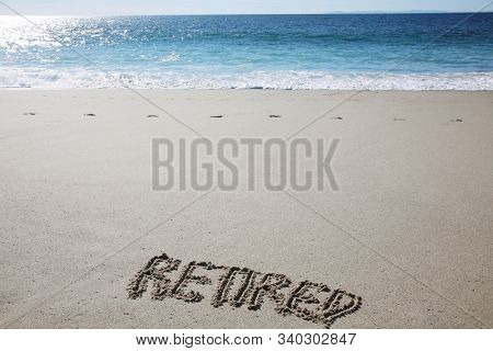 The word RETIRED written in the sand at the ocean.  Retirement gives you more time for fun vacation adventures like visiting the local beaches.