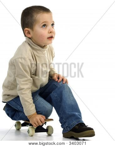 Young boy on kneeling on a skate board