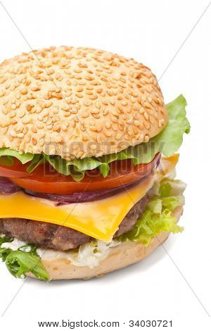 big tasty  cheeseburger with sesame seeds bun, cheddar cheese, spanish onion, tomato, mayonnaise and lettuce on white background close-up