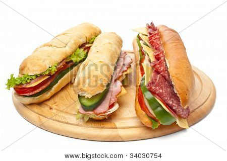 group of long baguette sandwiches with lettuce, vegetables, salami, ham and cheese on a cutting board