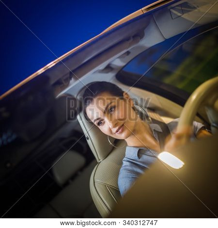 Pretty, young woman  driving a car -Invitation to travel. Car rental,  car ownership or vacation poster