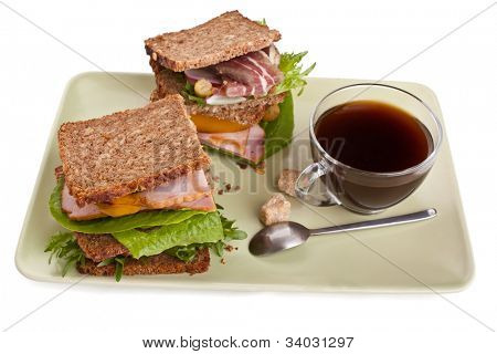 platter with coffee and two big healthy sandwiches made with whole grain bread, lettuce, vegetables and meat on white background