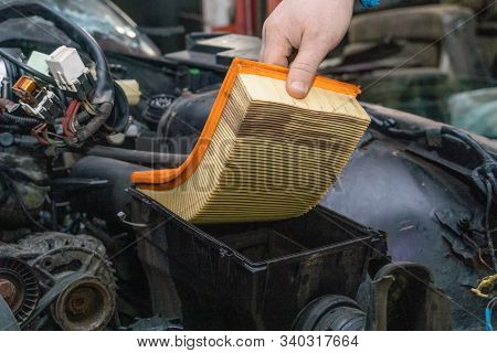 Replacing A Clogged Orange Car Air Filter During General Vehicle Maintenance With A Backup Plan