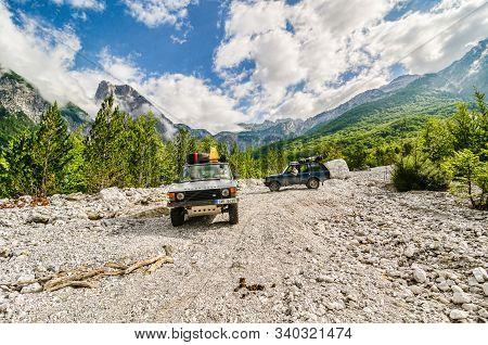Theth, Albania - July 24, 2014. Two Vintage Off Road Cars On The Dirt Road In Albanian Mountains