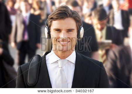 Male commuter in crowd wearing headphones
