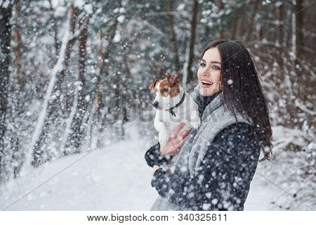 Look, Its Snowfall. Smiling Brunette Having Fun While Walking With Her Dog In The Winter Park.