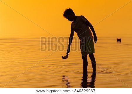 Little Boy Launching Paper Ships From Riverside. Floating Ships Into The Distance. Beautiful Sunset.