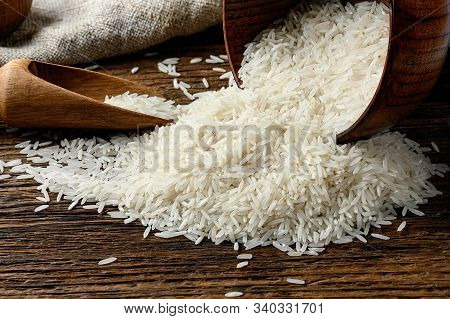 Still-life Of Uncooked Long Rice Spilled Out From The Bowl On Old Wooden Table.