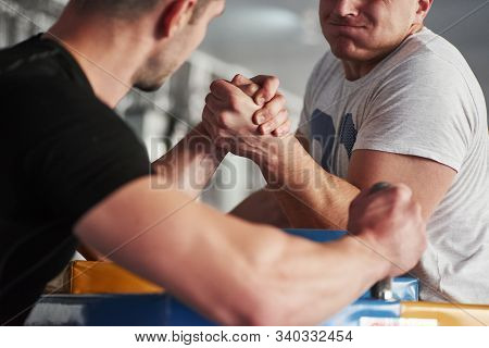 Close Up View. Arm Wrestling Challenge Between Two Men. Match On A Special Table.