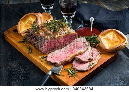 Traditional Commonwealth Sunday roast with sliced cold cuts roast beef with herbs and Yorkshire pudding closeup on a modern design wooden board