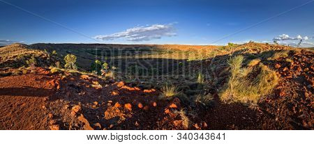 Large meteorite crater at the outback Australia – Wolf Creek crater with spinifex grass and boulders and blue sky as background in the morning sun
