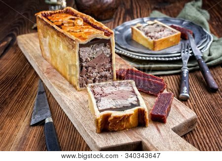 Traditional French Pate en croute with goose meat and liver ofered with quince cheese as closeup on a modern design wooden board