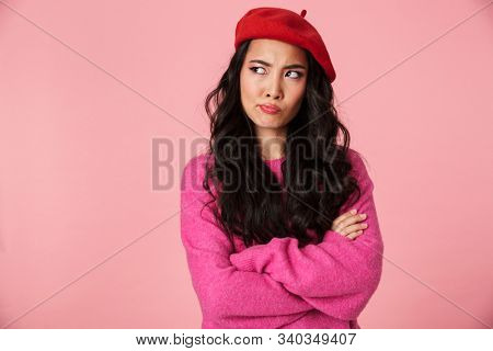 Image of discontent beautiful asian girl with long dark hair wearing beret standing with arms crossed isolated over pink background