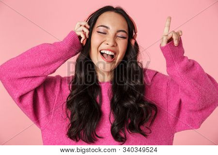 Image of optimistic beautiful asian girl with long dark hair pointing finger and listening to music with headphones isolated over pink background