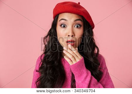 Image of scared beautiful asian girl with long dark hair wearing beret expressing fright isolated over pink background