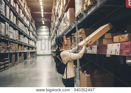 Asian Young Woman Choosing The Right Furniture Box For Her Apartment In A Modern Home Furnishings St