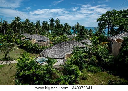 Huts Village Beside The Sea And Tropical Environment With The Cloudy Sky, Vacation Trip
