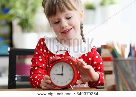 Portrait Of Smiling Little Kid Toying With Red Alarm-clock. Cheerful Child Wearing Polka-dot Dress A