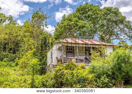 Old Country House/ Home In Rural Countryside Landscape. Bush/ Grass/ Trees Surround The Building Ext