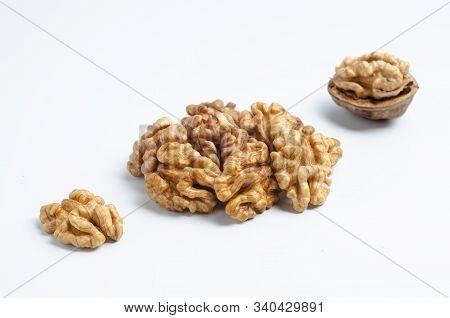 Three Walnuts Lying In A Diagonal Line, A Closed Walnut, Half Peeled Walnut And Half A Walnut.