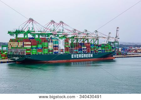Colon, Panama - December 8, 2019: Evergreen Container Ship With Full Of Cargo Docked In Port At Colo