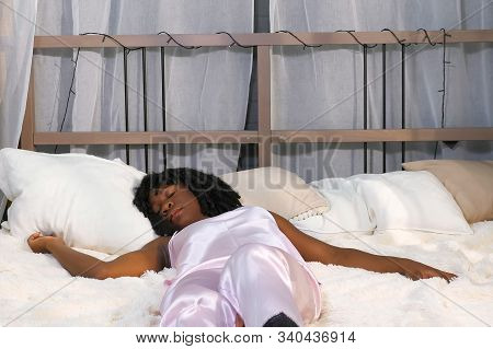 Attractive African American Girl With Curly Hair Lies On Large Bed And Wakes Up Suddenly In Stylish