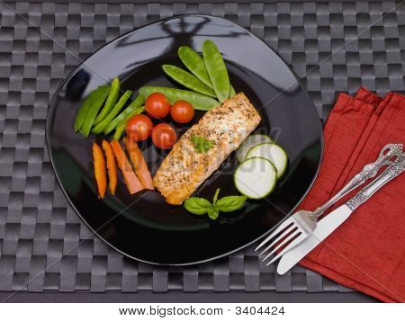 Salmon On Black Plate With Cutlery