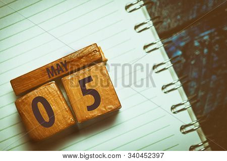 May 5th. Day 5 Of Month, Handmade Wood Cube With Date Month And Day Placed On A Lined Notebook On A