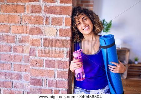 Young beautiful arab sportwoman smiling happy. Standing leaning on the wall  holding sport mat and bottle of water before class of yoga at gym